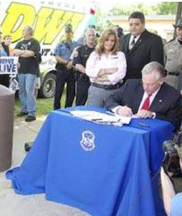 MADD leader Kerry Freeman watches Governor sign DWI law.